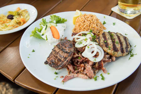 Greek mixed grill with grilled liver, Bifteki, Gyros, onions, tsatsiki, coleslaw and rice on wooden table Фото со стока