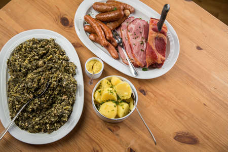 Traditional German winter dish Oldenburger green cabbage with sausage mix, Kassler pork neck on platter with boiled potatoes and mustard on wooden table
