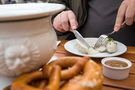Man eats Munich white sausage with knife and fork, sweet mustard and pretzel and take off sausage properly out of gut outside in beer garden