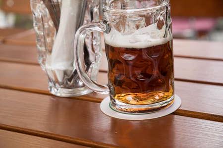 Glass dark German Vollbier beer in beer garden during summer on wooden table background