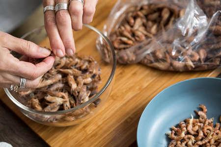 Woman peeling German Friesland north sea shrimps or crabs in domestic kitchen