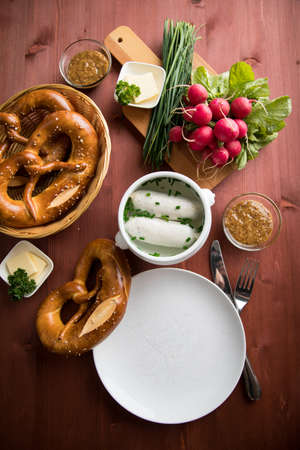 German Weißwurst white sausage in porcelain pot, Bavarian sweet mustard, butter, chives, radish and pretzel on wooden table