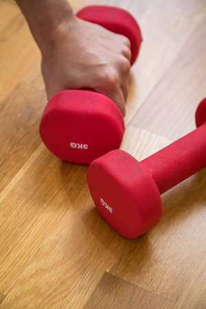 Woman using pair of red 3kg dumbbells for fitness training workout