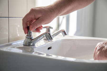 Man using washbasin with tap water for washing hands