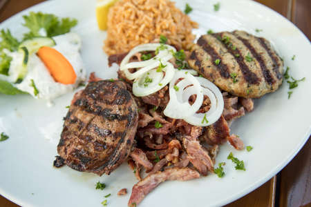Greek mixed grill with grilled liver, Bifteki, Gyros, onions, Tsatsiki and rice on wooden table Фото со стока