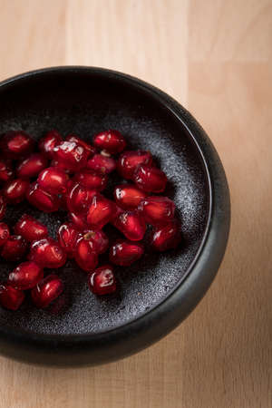 Red pomegranate seeds in black porcelain bowl on wooden background