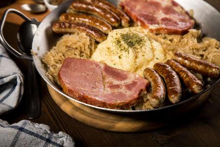 Sauerkraut pan with small fried Bavarian German Nürnberger sausages, smoked Kassler pork neck, mashed potatoes and mustard on wooden table