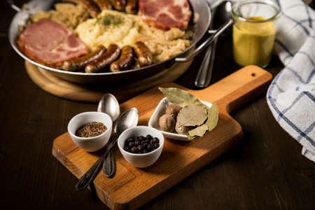 Sauerkraut spices bay, leaf, juniper, berries, caraway, seeds, nutmeg, with kraut pan, fried German Nürnberger sausages, Kassler pork neck, mashed potatoes, mustard on wooden table 免版税图像