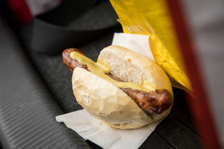 Typical grilled German Bratwurst sausage street food with bread roll bun and mustard in car on the go