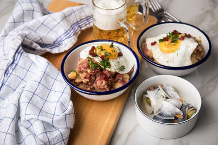 North German Hamburg Labskaus is a delicacy with corned beef, potatoes, beetroot, pickled gherkins, fried egg, herring and beer on marble table
