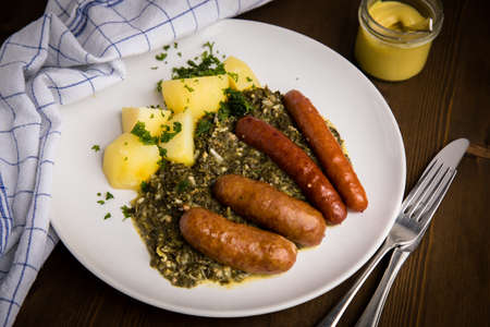 Traditional German Oldenburger green cabbage with smoked pork sausage mix, mustard and boiled potatoes on wooden table