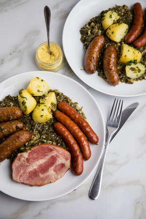 Two portions of traditional German Oldenburger green cabbage with smoked sausage mix, Kassler pork neck, mustard and boiled potatoes