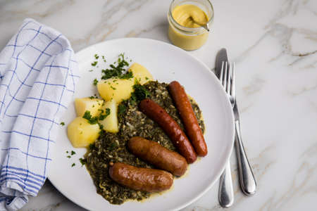 Traditional German Oldenburger green cabbage with smoked pork sausage mix, mustard and boiled potatoes on marble table
