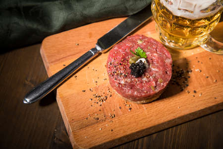 Gourmet beefsteak Tatar with lean raw beef fillet, capers, egg yolk, onions, toast bread, black caviar on wooden board with beer, green napkin and dark background