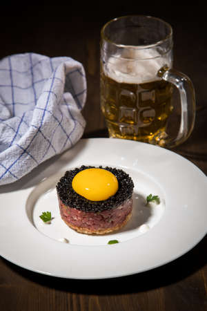 Gourmet beefsteak Tatar with lean raw beef fillet, capers, egg yolk, onions, toast bread, black caviar on porcelain plate with beer, kitchen towel and dark wooden background