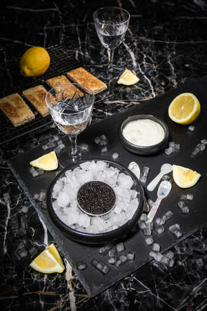 Black Sturgeon caviar on ice with pearl spoon, sour cream, toast, lemon and vodka in lead glass on slate plate and dark marble background