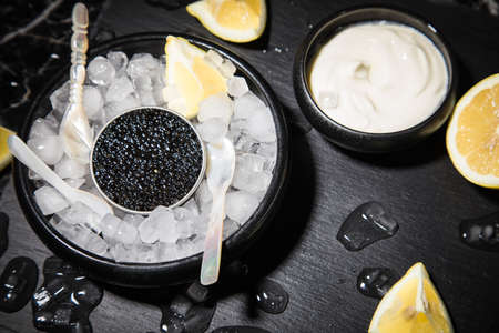 Black Sturgeon caviar on ice with pearl spoon, sour cream, lemon on slate plate and dark marble background Standard-Bild