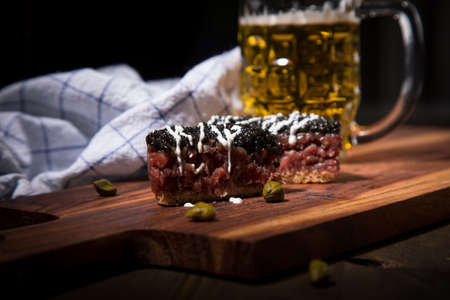 Gourmet beefsteak Tatar with lean raw beef filet, capers, egg yolk, onions, toast bread, black caviar, sour cream on wooden board with beer, kitchen towel and dark background
