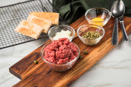 Gourmet beefsteak Tatar with lean raw beef fillet, capers, egg yolk, onions, toast bread on wooden board and light marble background