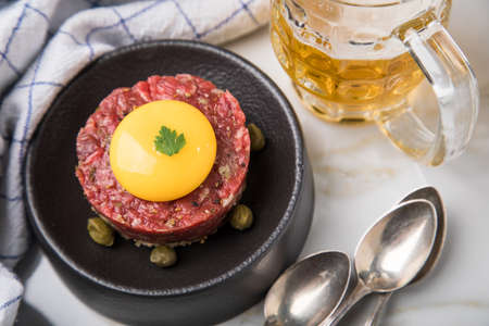Gourmet beefsteak Tatar with lean raw beef filet, capers, egg yolk, onions, toast bread on black plate with spoons, beer, kitchen towel and light marble background Standard-Bild