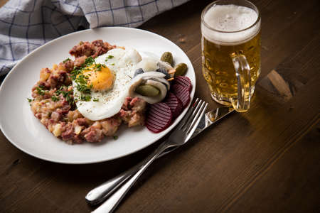 North German Hamburg Labskaus is a delicacy with corned beef, potatoes, beetroot, pickled gherkins, fried egg, herring and beer on wooden table