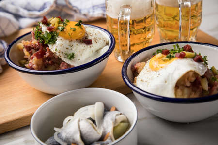 North German Hamburg Labskaus is a delicacy with corned beef, potatoes, beetroot, pickled gherkins, fried egg, herring and beer on marble table Standard-Bild