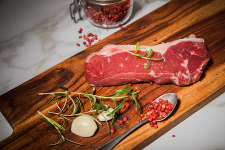 Fresh, raw beef rump steak with fat, rosemary, garlic, red pepper on wooden cutting board and light marble background Standard-Bild