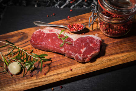 Fresh, raw beef rump steak with fat, rosemary, garlic, red pepper on wooden cutting board, black slate plate and dark marble background