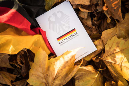 The book of German constitution basic law on flag of federal republic of Germany and fall autumn leaves Editorial