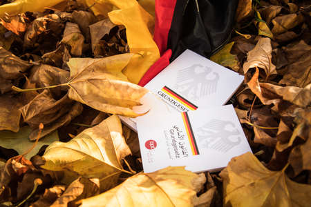 The constitution basic law book of Germany in German and Arabic language on flag and fall autumn leaves