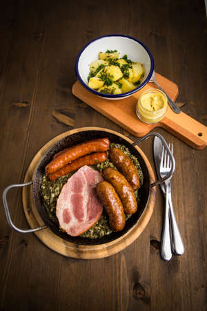 Traditional German Oldenburger green cabbage with smoked sausage mix, Kassler pork neck, mustard and boiled potatoes in cast iron pan on wooden table
