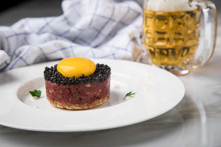 Gourmet beefsteak Tatar with lean raw beef fillet, capers, egg yolk, onions, toast bread, black caviar on porcelain plate with beer, kitchen towel and light marble background Standard-Bild