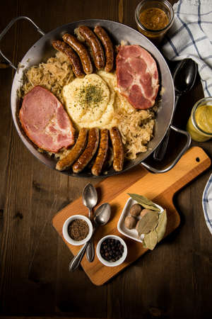 Sauerkraut pan with small fried Bavarian German Nürnberger sausages, smoked Kassler pork neck, mashed potatoes, mustard and spice ingredients on wooden table