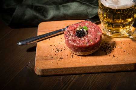 Gourmet beefsteak Tatar with lean raw beef fillet, capers, egg yolk, onions, toast bread, black caviar on wooden board with beer, green napkin and dark background Standard-Bild