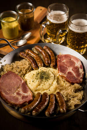 Sauerkraut pan with small fried Bavarian German Nürnberger sausages, smoked Kassler pork neck, mashed potatoes, mustard and beer on wooden table Standard-Bild