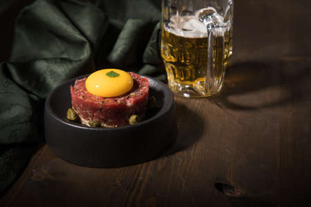 Gourmet beefsteak Tatar with lean raw beef fillet, capers, egg yolk, onions, toast bread on black plate with beer, green napkin and dark wooden background