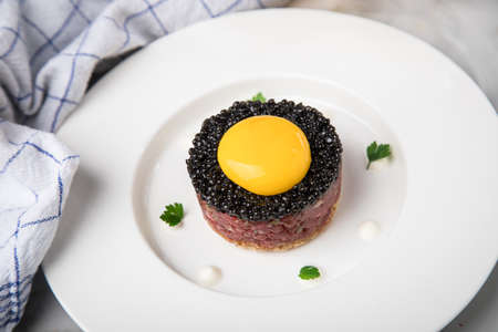 Gourmet beefsteak Tatar with lean raw beef fillet, capers, egg yolk, onions, toast bread, black caviar on porcelain plate on light marble background