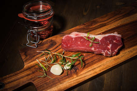 Fresh, raw beef rump steak with fat, rosemary, garlic, red pepper on cutting board and dark wooden table background