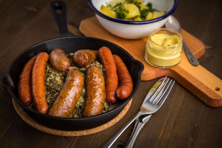 Traditional German Oldenburger green cabbage with smoked pork sausage mix, mustard and boiled potatoes in cast iron pan on wooden table