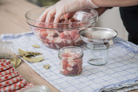 Woman filling bay leaves and raw pork shoulder with metal funnel and hygiene rubber gloves in preserving screw-cap glass jars for home-made pressure canning meat in domestic kitchen