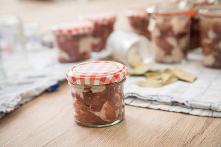 Raw pork shoulder with metal funnel in screw-cap and preserving mason glass jars on towel for home-made pressure canning meat as Russian specialty Tuschonka in domestic kitchen