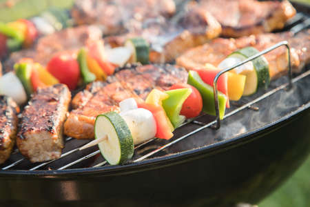 Marinated pork neck steak meat and colorful vegetable skewers roasting on kettle barbecue grill with charcoal and smoke in garden on summer evening
