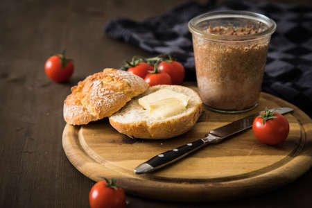 Canned liver sausage spread from long term pantry with crispy bread roll bun, butter, tomatoes and knife for snack or breakfast on cutting board and dark wooden background Standard-Bild