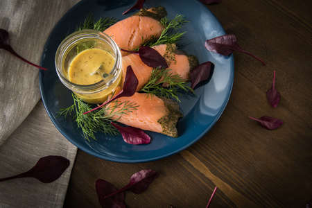 Gravlax graved salmon with beet root leaves salad, dill, Scandinavian mustard sauce on dark blue plate and wooden background with linen towel as appetizer or snack