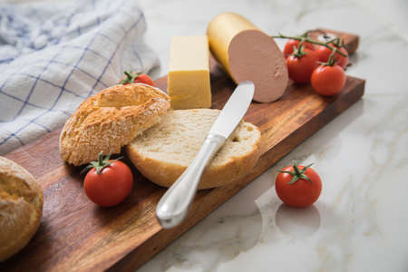 German fine veal liver sausage spread with two crispy bread rolls buns, tomatoes, butter and knife on wooden board, kitchen towel and light marble background for breakfast Standard-Bild