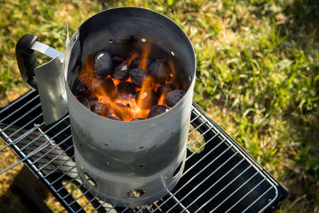 Coal of charcoal grill burning in flames with fire and lighter in barbecue chimney for BBQ evening