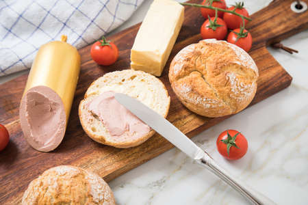 German fine veal liver sausage spread on crispy bread roll bun, with butter, tomatoes, wooden board, kitchen towel and light marble background for breakfast or supper