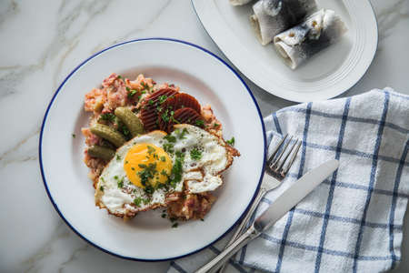 North German Hamburg Labskaus is a delicacy with corned beef, potatoes, beetroot, pickled gherkins, fried egg and herring on enamel plate Standard-Bild
