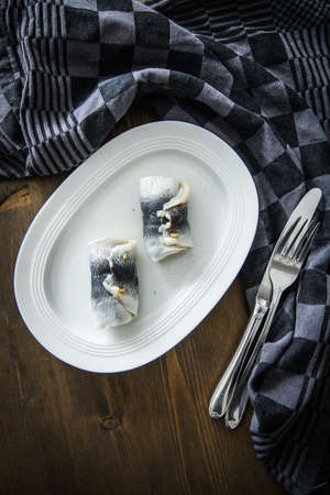 2 German Rollmops rolled pickled herring with gherkin onion filling on porcelain plate with cutlery, kitchen towel and dark wooden background Standard-Bild