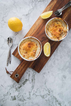 Traditional Eastern Germany DDR GDR cuisine -Würzfleisch or Ragout Fin a pork and poultry meat meal in light roux sauce with cheese gratin and lemon on wooden board and light marble background